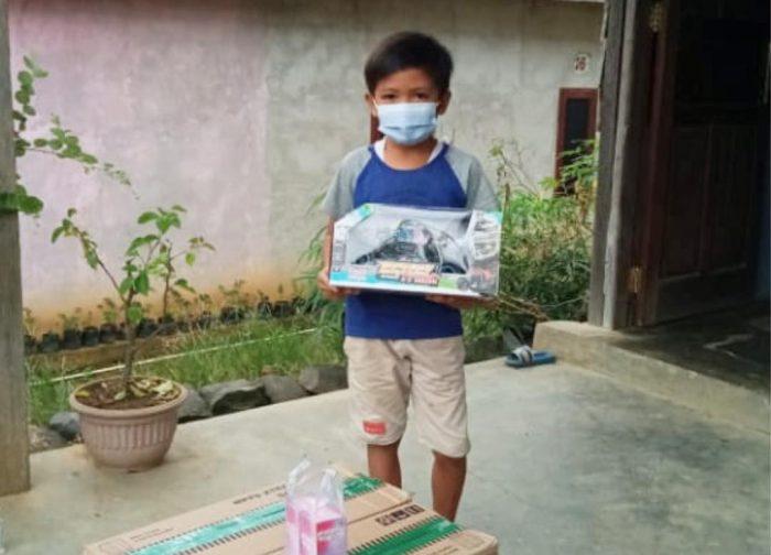 Alviano Dafa Raharjo alias Vino, bocah yatim piatu di Kutai Barat menggendong mainan yang diberikan para warga yang menaruh empati kepadanya. Foto : BorneoFlash.com/Lilis Suryani.