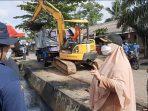 Pengerukan sampah drainase menggunakan excavator mini yang dilakukan Pemerintah Kabupaten Paser bersama masyarakat saat kegiatan bersih-bersih lingkungan yang juga di dihadiri Wakil Bupati (Wabup) Paser Hj. Syarifah Masitah Assegaf pada Minggu (8/8/2021). Foto : BorneoFlash.com/Fitriani.