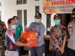 Kepala Dinas Sosial Kubar, Ampeng menyerahkan bantuan paket sembako secara simbolis kepada warga di Kampung Tanjung Isuy yang sedang menjalani Isoman akibat covid-19. Foto ; BorneoFlash.com/Lilis Suryani.